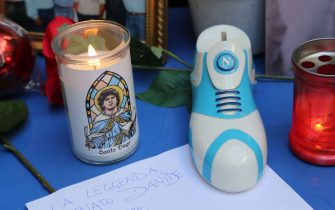 """A candle reading """"Holy Diego"""" and a shoe with the logo of SSC Napoli football club are pictured by a small altar where people gather to mourn Argentinian football legend Diego Maradona on November 26, 2020 in the Spanish quarters of Naples, a day after the death of Maradona. - Maradona, widely remembered for his """"Hand of God"""" goal against England in the 1986 World Cup quarter-finals, died on November 25, 2020 of a heart attack at his home near Buenos Aires in Argentina, while recovering from surgery to remove a blood clot on his brain. (Photo by Carlo Hermann / AFP) (Photo by CARLO HERMANN/AFP via Getty Images)"""