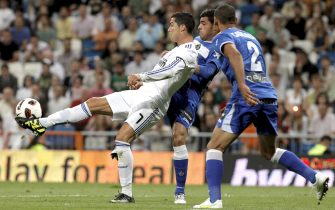epa02726395 Real Madrid's Portuguese striker Cristiano Ronaldo (L) is challenged for the ball by Miguel Torres and Argentinian Daniel 'Cata' Diaz (R), both of Getafe during the Spanish Primera Division soccer match at Santiago Bernabeu stadium in Madrid, central Spain, on 10 May 2011.  EPA/JUANJO MARTIN