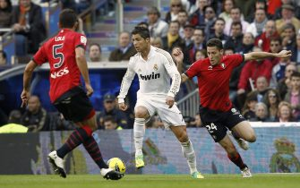 epa02994290 Real Madrid's Portuguese striker Cristiano Ronaldo (C) fights for the ball with Spaniards Manuel Jesus Ortiz Toribio 'Lolo' (L) and Damia Abella, of CA Osasuna team, during the First Division League's match at Santiago Bernabeu's stadium on 06 November 2011 in Madrid, Spain.  EPA/BALLESTEROS