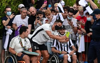 Juventus' Portuguese forward Cristiano Ronaldo poses with fans as arrives for his medical examination at the club's Continassa training ground in Turin, on July 26, 2021. - Ronaldo medical examination (Photo by MIGUEL MEDINA / AFP) (Photo by MIGUEL MEDINA/AFP via Getty Images)