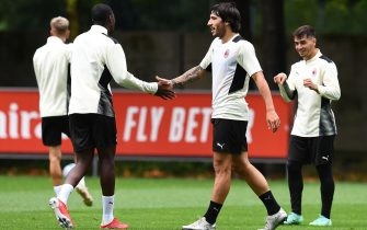 CAIRATE, ITALY - JULY 27: Fode Ballo-Toure shakes hands with Sandro Tonali attends an AC Milan Training Session at Milanello on July 27, 2021 in Cairate, Italy. (Photo by Claudio  Villa/AC Milan via Getty Images)