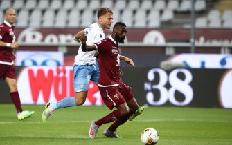 Lazio's Italian forward Ciro Immobile (2ndL) shoots to score an equalizer  despite Torino's Cameroonian defender Nicolas N'Koulou during the Italian Serie A football match Torino vs Lazio played on June 30, 2020 behind closed doors at the Olympic stadium in Turin, as the country eases its lockdown aimed at curbing the spread of the COVID-19 infection, caused by the novel coronavirus. (Photo by Isabella BONOTTO / AFP) (Photo by ISABELLA BONOTTO/AFP via Getty Images)