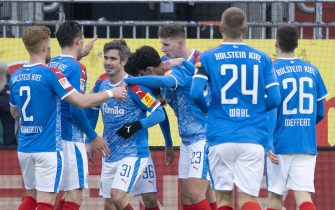 30 January 2021, Schleswig-Holstein, Kiel: Football: 2. Bundesliga, Holstein Kiel - Eintracht Braunschweig, Matchday 19. Kiel's players celebrate Kiel's Fin Bartels (3rd from left) for his goal to make it 2:0. Photo: Axel Heimken/dpa - IMPORTANT NOTE: In accordance with the regulations of the DFL Deutsche Fußball Liga and/or the DFB Deutscher Fußball-Bund, it is prohibited to use or have used photographs taken in the stadium and/or of the match in the form of sequence pictures and/or video-like photo series.