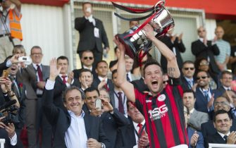 UEFA President Michel Platini (L) waves after giving the trophy to Lincoln Red Imps FC's captain following the Gibraltar Cup final football match Lincoln Red Imps FC vs College Europa FC at the Victoria Stadium in Gibraltar on May 10, 2014.  AFP PHOTO / MARCOS MORENO        (Photo credit should read MARCOS MORENO/AFP/Getty Images)