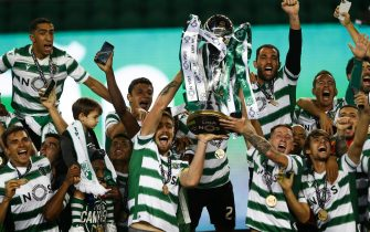 epa09192620 Sporting Lisbon's players hold the trophy as they celebrate the Portuguese First League title after defeating Boavista FC in their match held at Alvalade Stadium, Lisbon, Portugal, 11 May 2021.  EPA/ANTONIO COTRIM