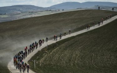 The pack rides through a dusty gravel road during the one-day classic cycling race Strade Bianche (White Roads) on March 9, 2019 around Siena, Tuscany. (Photo by Marco BERTORELLO / AFP)        (Photo credit should read MARCO BERTORELLO/AFP via Getty Images)