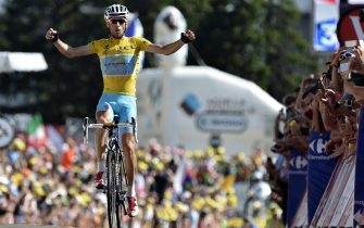 Italy's Vincenzo Nibali wearing the overall leader's yellow jersey celebrates as he crosses the finish line at the end of the 197.5 km thirteenth stage of the 101st edition of the Tour de France cycling race on July 18, 2014 between Saint-Etienne and Chamrousse, central eastern France.  AFP PHOTO / JEFF PACHOUD        (Photo credit should read JEFF PACHOUD/AFP via Getty Images)