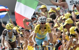 France's Jean-Christophe Peraud (L) and Italy's Vincenzo Nibali wearing the overall leader's yellow jersey sprint to cross the finish line, riding past an Italian national flag at the end of the 177 km fourteenth stage of the 101st edition of the Tour de France cycling race on July 19, 2014 between Grenoble and Risoul, eastern France. Poland's Rafal Majka won the stage.  AFP PHOTO / JEFF PACHOUD        (Photo credit should read JEFF PACHOUD/AFP via Getty Images)