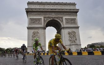 Italy's Vincenzo Nibali, wearing the overall leader's yellow jersey, rides past the Arc de Triomphe in the pack during the 137.5 km twenty-first and last stage of the 101st edition of the Tour de France cycling race on July 27, 2014 between Evry and Paris.  AFP PHOTO / JEFF PACHOUD        (Photo credit should read JEFF PACHOUD/AFP via Getty Images)