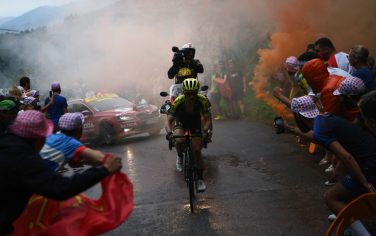 TOPSHOT - Great Britain's Simon Yates leads the race as as orange smoke billows in the last kilometers during the fifteen stage of the 106th edition of the Tour de France cycling race between Limoux and Foix Prat d'Albis, in Foix Prat d'Albis on July 21, 2019. (Photo by Anne-Christine POUJOULAT / AFP)        (Photo credit should read ANNE-CHRISTINE POUJOULAT/AFP via Getty Images)