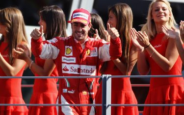 MONZA, ITALY - SEPTEMBER 12:  Fernando Alonso of Spain and Ferrari celebrates on his way to the podium after winning the Italian Formula One Grand Prix at the Autodromo Nazionale di Monza on September 12, 2010 in Monza, Italy.  (Photo by Paul Gilham/Getty Images)