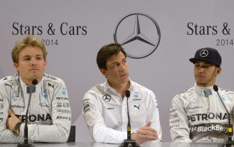 """Mercedes-AMG's F1 British driver Lewis Hamilton (R) and his German teammate Nico Rosberg (L) attend a press conference with Mercedes AMG Executive Director Torger Christian """"Toto"""" Wolff (C) at the Mercedes-Benz """"Stars & Cars 2014"""" event in Stuttgart, southwestern Germany, on November 29, 2014.  AFP PHOTO / THOMAS KIENZLE        (Photo credit should read THOMAS KIENZLE/AFP/Getty Images)"""