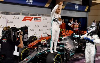 TOPSHOT - Mercedes' British driver Lewis Hamilton (C) celebrates after winning the Formula One Bahrain Grand Prix at the Sakhir circuit in the desert south of the Bahraini capital Manama, on March 31, 2019. (Photo by Andrej ISAKOVIC / AFP)        (Photo credit should read ANDREJ ISAKOVIC/AFP/Getty Images)
