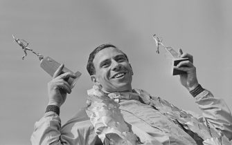 British Formula One racing driver Jim Clark (1936-1968) celebrates on the podium with two statuettes after finishing in first place in the #4 Team Lotus Lotus 25 Climax V8 to win the 1963 British Grand Prix at Silverstone Circuit in Northamptonshire, England on 20th July 1963. (Photo by Blackman/Express/Hulton Archive/Getty Images)