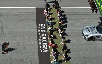 """Drivers kneel behind a banner reading """"End Racism"""" ahead the Austrian Formula One Grand Prix race on July 5, 2020 in Spielberg, Austria. (Photo by Joe Klamar / various sources / AFP) (Photo by JOE KLAMAR/AFP via Getty Images)"""