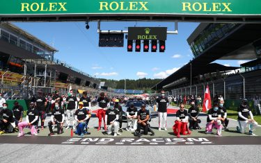 """Drivers kneel behind a banner reading """"End racism"""" ahead the Austrian Formula One Grand Prix race on July 5, 2020 in Spielberg, Austria in solidarity with the """"Black Lives Matter"""" movement. (Photo by Dan ISTITENE / POOL / AFP) (Photo by DAN ISTITENE/POOL/AFP via Getty Images)"""