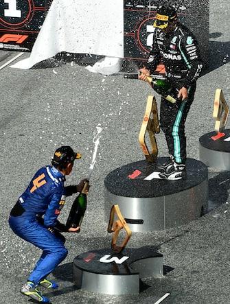 Mercedes' Finnish driver Valtteri Bottas (R) and McLaren's British driver Lando Norris spray champagne on the podium of the Austrian Formula One Grand Prix race on July 5, 2020 in Spielberg, Austria. (Photo by JOE KLAMAR / various sources / AFP) (Photo by JOE KLAMAR/POOL/AFP via Getty Images)