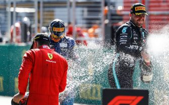(L to R) Ferrari's Monegasque driver Charles Leclerc, McLaren's British driver Lando Norris and Mercedes' Finnish driver Valtteri Bottas celebrate with champagne on the podium of the Austrian Formula One Grand Prix race on July 5, 2020 in Spielberg, Austria. (Photo by LEONHARD FOEGER / POOL / AFP) (Photo by LEONHARD FOEGER/POOL/AFP via Getty Images)