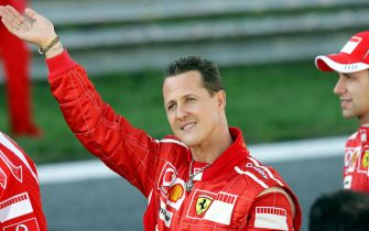 Monza, ITALY:  German Ferrari driver Michael Schumacher (L) waves to fans next to test-driver Luca Badoer during the Ferrari exhibition at the F1 race track in Monza 29 October 2006. The 37-year-old Schumacher, who retired as a driver after piloting his Ferrari to fourth place in the Brazilian Grand Prix last Sunday, is to stay with Ferrari as assistant to new chief executive officer Jean Todt.    AFP PHOTO / VINCENZO PINTO  (Photo credit should read VINCENZO PINTO/AFP via Getty Images)