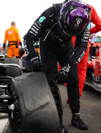 Mercedes' British driver Lewis Hamilton inspects his punctured tyre in parc ferme after victory in the Formula One British Grand Prix at the Silverstone motor racing circuit in Silverstone, central England on August 2, 2020. - Lewis Hamilton wins record seventh British Grand Prix . (Photo by Bryn Lennon / POOL / AFP) (Photo by BRYN LENNON/POOL/AFP via Getty Images)
