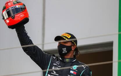 Lewis, casco di Schumi in trionfo sul podio. FOTO
