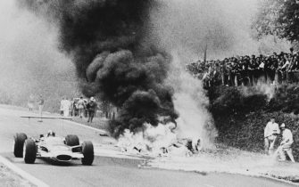 Graham Hill driving the #12 Gold Leaf Team Lotus 49B passes the fire from the burning magnesium chassis Honda Racing (France) Honda RA302 Honda V8 of Jo Schlesser of France who was killed on the second lap of the French Grand Prix on 7th July 1968 at the Rouen-Les-Essarts Circuit in Rouen, France. (Photo by AFP/Central Press/Hulton Archive/Getty Images)