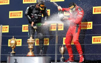 Mercedes' British driver Lewis Hamilton (L) and third placed Ferrari's Monegasque driver Charles Leclerc (R) spray the champagne on the winners' podium after winning the Formula One British Grand Prix at the Silverstone motor racing circuit in Silverstone, central England on August 2, 2020. - Lewis Hamilton survived a dramatic finale to win the British Grand Prix on Sunday, just making it across the line on three tyres to beat a fast closing Max Verstappen on Red Bull. The defending world champion claimed his seventh British Grand Prix win as Ferarri's Charles Leclerc came third and Daniel Ricciardo of Renault fourth. (Photo by ANDREW BOYERS / POOL / AFP) (Photo by ANDREW BOYERS/POOL/AFP via Getty Images)