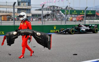 SOCHI, RUSSIA - SEPTEMBER 26: Sebastian Vettel of Germany and Ferrari retrieves his front wing from the track after crashing as Lewis Hamilton of Great Britain driving the (44) Mercedes AMG Petronas F1 Team Mercedes W11 passes during qualifying ahead of the F1 Grand Prix of Russia at Sochi Autodrom on September 26, 2020 in Sochi, Russia. (Photo by Getty Images/Getty Images)