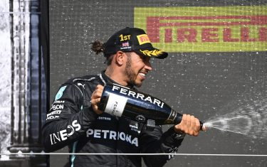 SILVERSTONE CIRCUIT, UNITED KINGDOM - JULY 18: Sir Lewis Hamilton, Mercedes, 1st position, sprays the victory Champagne during the British GP at Silverstone Circuit on Sunday July 18, 2021 in Northamptonshire, United Kingdom. (Photo by Mark Sutton / Sutton Images)