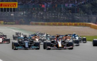 SILVERSTONE CIRCUIT, UNITED KINGDOM - JULY 18: Max Verstappen, Red Bull Racing RB16B, and Sir Lewis Hamilton, Mercedes W12, lead the field away at the start during the British GP at Silverstone Circuit on Sunday July 18, 2021 in Northamptonshire, United Kingdom. (Photo by Steven Tee / LAT Images)