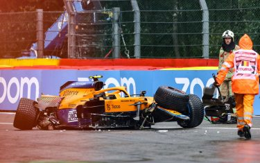 TOPSHOT - Race marshalls and technicians clear the car McLaren's British driver Lando Norris after he crashed unthe qualifying session of the Formula One Belgian Grand Prix at the Spa-Francorchamps circuit in Spa on August 28, 2021. (Photo by KENZO TRIBOUILLARD / AFP) (Photo by KENZO TRIBOUILLARD/AFP via Getty Images)