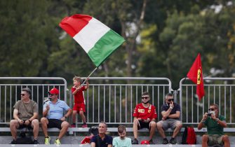 AUTODROMO NAZIONALE MONZA, ITALY - SEPTEMBER 10: A young fan waves an Italian flag from a grandstand during the Italian GP at Autodromo Nazionale Monza on Friday September 10, 2021 in Monza, Italy. (Photo by Charles Coates / LAT Images)