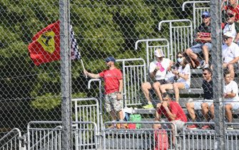 AUTODROMO NAZIONALE MONZA, ITALY - SEPTEMBER 11: A Ferrari fan waves a flag in a grandstand during the Italian GP at Autodromo Nazionale Monza on Saturday September 11, 2021 in Monza, Italy. (Photo by Mark Sutton / Sutton Images)