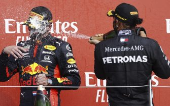 epa08593632 Winner Dutch Formula One driver Max Verstappen of Aston Martin Red Bull Racing (L) and second British Formula One driver Lewis Hamilton of Mercedes-AMG Petronas (R) celebrate on the podium after the 70th Anniversary Formula One Grand Prix of Great Britain at the Silverstone Circuit, in Northamptonshire, Britain, 9 August 2020.  EPA/Andrew Boyers / Pool
