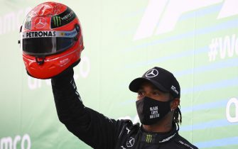 epa08735698 Winner British Formula One driver Lewis Hamilton of Mercedes-AMG Petronas (L) celebrates holding F1 legend Michael Schumacher's helmet, handed to him by Michael's son Mick Schumacher, after the 2020 Formula One Eifel Grand Prix at the Nuerburgring race track in Nuerburg, Germany, 11 October 2020.  EPA/Bryn Lennon / Pool