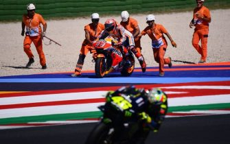 Race marshalls help Repsol Honda Team Spanish rider, Marc Marquez (Rear C) pick his motorbike after he fell, as Monster Energy Yamaha Italian rider, Valentino Rossi (Front) rides past during a free practice session ahead of the San Marino MotoGP Grand Prix race at the Misano World Circuit Marco Simoncelli on September 14, 2019. (Photo by Marco Bertorello / AFP)        (Photo credit should read MARCO BERTORELLO/AFP via Getty Images)