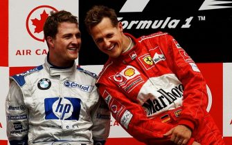 Formula One Canadian Grand Prix winner Ferrari driver Michael Schumacher (R) of Germany talks to his brother, second place finisher Williams driver Ralf Schumacher (L) of Germany, on the podium, 15 June, 2003,  at the Circuit Gilles-Villeneuve in Montreal, Canada.   AFP PHOTO/Stan HONDA        (Photo credit should read STAN HONDA/AFP via Getty Images)