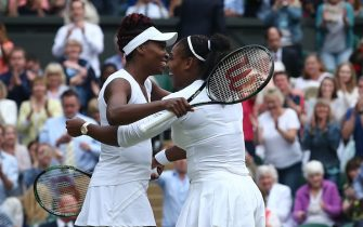 US player Serena Williams (R) embraces her partner US player Venus Williams (L) as they celebrate beating Hungary's Timea Babos and Kazakhstan's Yaroslava Shvedova to win the women's doubles final on the thirteenth day of the 2016 Wimbledon Championships at The All England Lawn Tennis Club in Wimbledon, southwest London, on July 9, 2016. / AFP / JUSTIN TALLIS / RESTRICTED TO EDITORIAL USE        (Photo credit should read JUSTIN TALLIS/AFP via Getty Images)