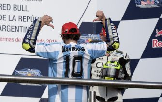 Italy's biker Valentino Rossi of Yamaha wears a jersey of the Argentine football team with the name of former star Diego Maradona on it, as he celebrates on the podium after winning the Argentina Grand Prix at Termas de Rio Hondo circuit, in Santiago del Estero, on April 19, 2015. Valentino Rossi survived a late battle with defending world champion Marc Marquez, who crashed with two laps to go.  AFP PHOTO / JUAN MABROMATA        (Photo credit should read JUAN MABROMATA/AFP via Getty Images)
