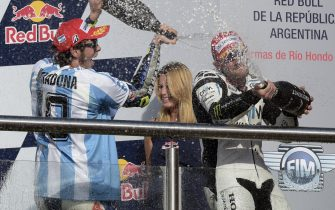 Italy's biker Valentino Rossi (L) of Yamaha sprays champagne over British Carl Crutchlow of Honda who came third, as he celebrates on the podium after winning the Argentina Grand Prix at Termas de Rio Hondo circuit, in Santiago del Estero, on April 19, 2015. Valentino Rossi survived a late battle with defending world champion Marc Marquez, who crashed with two laps to go.  AFP PHOTO / JUAN MABROMATA        (Photo credit should read JUAN MABROMATA/AFP via Getty Images)