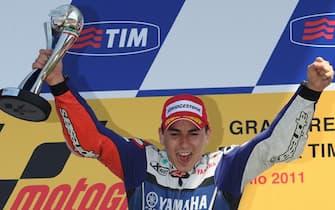 epa02808336 Spanish rider Jorge Lorenzo (c) of Team  Honda celebrates on the podium  first  place in the Moto GP of the Grand Prix of Italy at the Mugello circuit, central Italy, 03 July 2011.  EPA/CARLO FERRARO