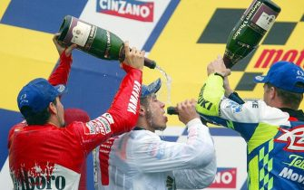 Italian Valentino Rossi (C), of Honda RCV, is sprayed with champagne by Italian Max Piagg, of Yamaha (L) and by US Kenny Roberts, of Suzuki, celebrating Rossi's victory, 21 September, 2002, at the Rio's Moto GP, in Rio de Janeiro, Brazil. Valentino won the race and obtained the 2002 MotoGP championship, while Biaggi arrived second and Roberts, third.   AFP PHOTO/MAURICIO LIMA (Photo by MAURICIO LIMA / AFP) (Photo by MAURICIO LIMA/AFP via Getty Images)