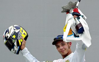SEPANG, MALAYSIA:  Valentino Rossi of Italy celebrates with his trophy after winning the Malaysian Motorcycle Grand Prix in Sepang 12 October 2003. Rossi won the race with a time of 43:41.457 to become the World MotoGP Champion, his third championship in a row.  AFP PHOTO / Jimin LAI  (Photo credit should read JIMIN LAI/AFP via Getty Images)