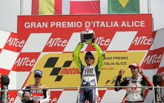 mugello, ITALY: Italian Valentino Rossi surrounded by Spanish Dani Pedrosa (L) and Alex Barros of Brazil celebrates on the podium of Italian MotoGP Grand Prix at Mugello's race track, 03 June 2007. Italian superstar Valentino Rossi won the Italian MotoGP to maintain his 100percent record in his home race. The Yamaha rider beat home Spain's Dani Pedrosa while veteran Alex Barros of Brazil was third. AFP PHOTO / ALBERTO PIZZOLI (Photo credit should read ALBERTO PIZZOLI/AFP via Getty Images)