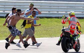 Il pilota Valentino Rossi in pista con un gruppo di suoi fans dopo il secondo posto nella gara della MotoGP nel circuito di Misano Adriatico, 16 settembre 2012. ANSA/ PASQUALE BOVE