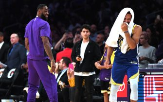 LOS ANGELES, CALIFORNIA - OCTOBER 14:  LeBron James #23 of the Los Angeles Lakers and Stephen Curry #30 of the Golden State Warriors laugh on the sidelines during a timeout in a 104-98 Lakers preseason win at Staples Center on October 14, 2019 in Los Angeles, California. (Photo by Harry How/Getty Images)