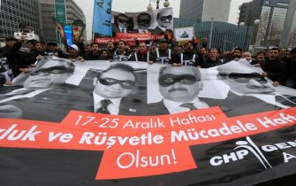 "Supporters of main opposition party Republican People's Party (CHP) hold a banner bearing pictures of four former ministers during a protest in Ankara, on December 17, 2014 The banner reads: ""December 17-25. Week to promote fight against corruption and bribery"". Pictures of former ministers on the banner are (L-R): Muammer Guler of Interior, Egemen Bagis of European Affairs, Zafer Caglayan of Economy and Erdogan Bayraktar of Environment and City Planning. AFP PHOTO/ADEM ALTAN        (Photo credit should read ADEM ALTAN/AFP/Getty Images)"