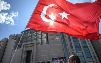 Protesters hold up the Turkish national flag in front of Caglayan court house in Istanbul on July 18, 2019, as they demonstrate in support of Republican People's Party (CHP) Istanbul chief Canan Kaftancioglu, who faces up to 17 years in prison for allegedly 'insulting the Turkish President' in tweets posted between 2012 and 2017. - Kaftancioglu's trial resumes on July 18. (Photo by Ozan KOSE / AFP)        (Photo credit should read OZAN KOSE/AFP/Getty Images)