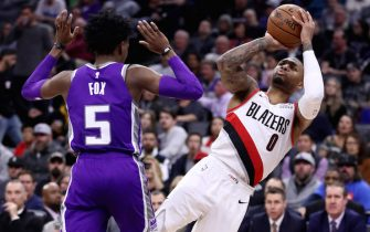 SACRAMENTO, CALIFORNIA - JANUARY 14:  Damian Lillard #0 of the Portland Trail Blazers is fouled by De'Aaron Fox #5 of the Sacramento Kings as he shoots the ball at Golden 1 Center on January 14, 2019 in Sacramento, California. NOTE TO USER: User expressly acknowledges and agrees that, by downloading and or using this photograph, User is consenting to the terms and conditions of the Getty Images License Agreement. (Photo by Ezra Shaw/Getty Images)