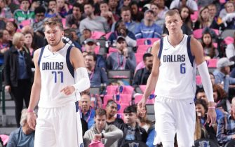 DALLAS, TX - OCTOBER 11: Luka Doncic #77, and Kristaps Porzingis #6 of the Dallas Mavericks looks on against the Milwaukee Bucks during a pre-season game on October 11, 2019 at the American Airlines Center in Dallas, Texas. NOTE TO USER: User expressly acknowledges and agrees that, by downloading and or using this photograph, User is consenting to the terms and conditions of the Getty Images License Agreement. Mandatory Copyright Notice: Copyright 2019 NBAE (Photo by Glenn James/NBAE via Getty Images)